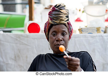 Woman is holding a lollipop in her hand