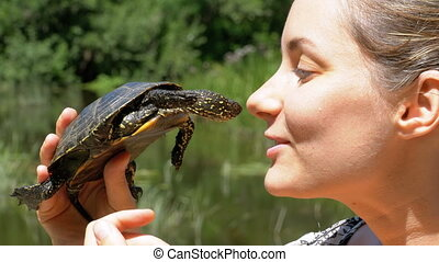Woman is Holding a Small River Turtle in her Hands near Face on Nature and River Background
