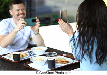 Woman is holding smartphone in her hands, man is filming review of novelty on smartphone in cafe. Tests and video reviews of new concept products
