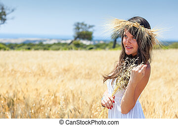 Woman is in the field with a wreath