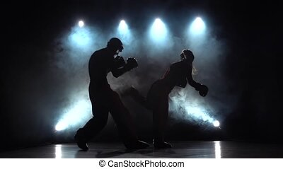 Woman is kicking a guy with their sparring kickboxing. Smoke...