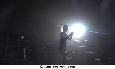 Woman is kicking in the ring. Silhouette. Slow motion