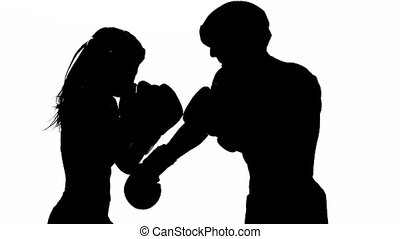 Woman is kicking the guy they are sparring for kickboxing ....