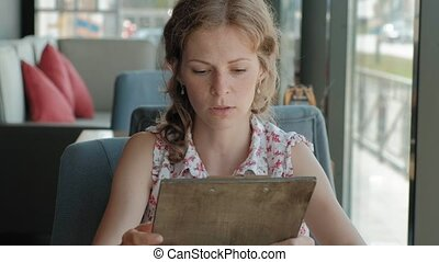Woman is looking through the menu at the restaurant