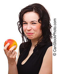 Young attractive woman is making sour face after biting red apple, isolated over white