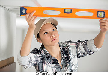woman is measuring the level of a ceiling