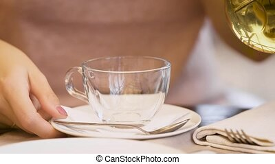 woman is pouring a green tea into glass cup in the restaraunt on summer holiday