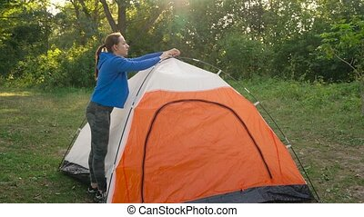 Woman is putting a tourist tent in the forest - Woman is...