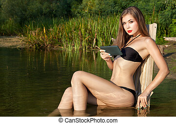 Woman is resting nature with a tablet in her hand.