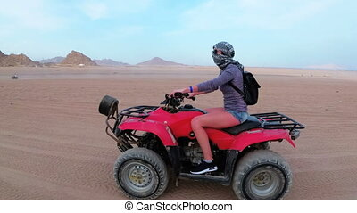 Woman is Riding a Quad Bike in the Desert of Egypt. Dynamic...