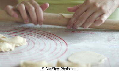 woman is rolling a dough with a rolling pin, clouse up -...