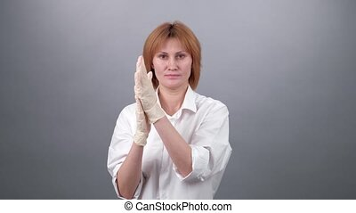woman is rubbing the hand in medical gloves on her hands. COVID-19.
