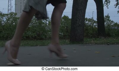 Woman is running away in the evening on the street low angle feet view in slow motion gimbal shot