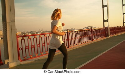 woman is running by the balustrade - female runner is having...