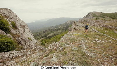 Woman is running in mountains over the sea. Running, sports, fitness and healthy lifestyle outdoors in summer nature