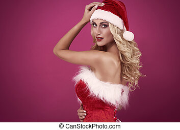 Woman is santa's clothing looking at camera