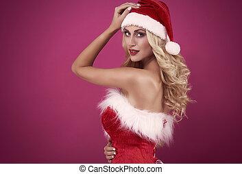 Woman is santa's clothing looking at camera
