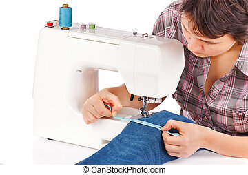 Woman is sewing on the sewing machine on a white background