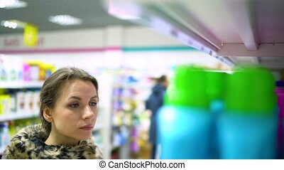 Woman is shopping in the store household chemicals and cosmetics