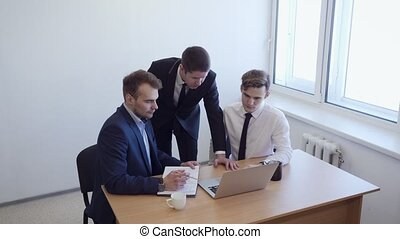 Woman is sitting at the desk, the team is standing around her.