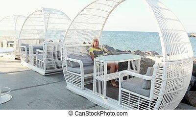 woman is sitting down in chair on a terrace near sea