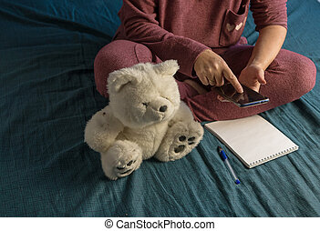 Woman is sitting in a tracksuit on a bed at home. Plan your day in Notepad. Color of bed linen tidewater green, trend 2021.