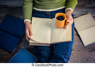 woman is sitting on a wooden floor and reading a book while holding a coffee cup