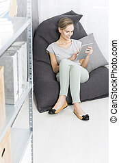 Woman is sitting on modern pouf