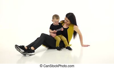 Woman is sitting on the floor with her baby, she is stroking his hair. White background. Slow motion