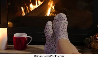 Woman is sitting with cup of hot drink and book near the...
