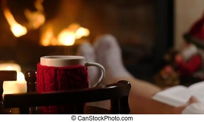 Woman is resting with cup of hot drink and book near the fireplace