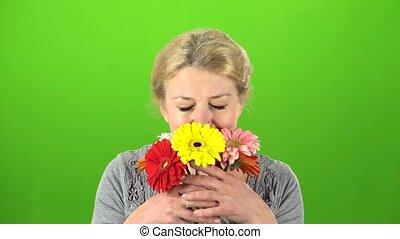 Woman is sniffing flowers. Green screen - Elderly woman...