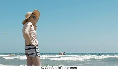 Woman is standing at the beach with a jute hat on - A woman...