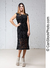 Woman is standing in a black evening dress studio