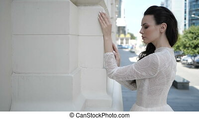 Woman is standing next to the wall