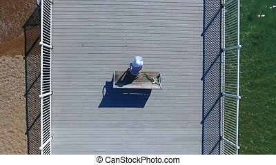 Woman is standing up from the bench and walking on the wooden pier to the fence. Woman is wearing white sun hat on the pier. Shooting from above.