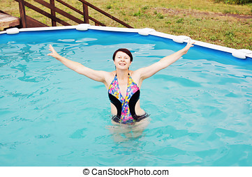 Woman is swimming in a little outdoor pool