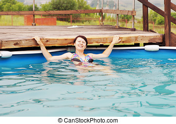 Woman is swimming in an outdoor pool