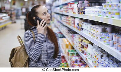 woman is talking on phone at grocery store - girl is talking...