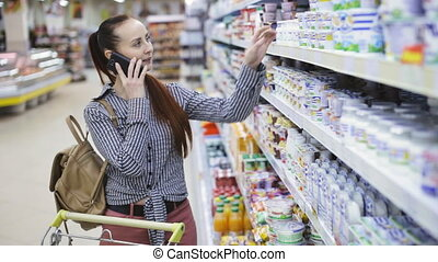 woman is talking on the phone at the grocery store - girl is...