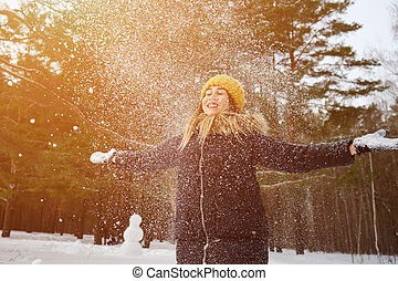 Woman is throwing some snow in the air enjoying the cold season