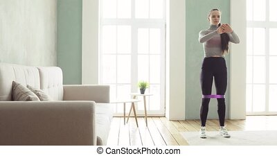 Woman is training making squats exercises at home in living room, front view.