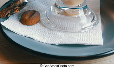 Woman is turning a saucer and a glass with a latte in a...
