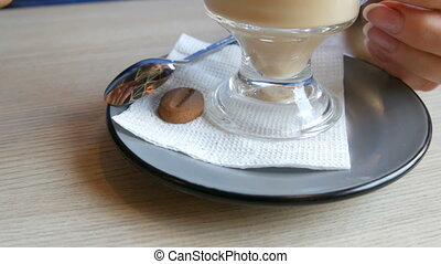 Woman is turning a saucer and a glass with a latte in a cafe, on the saucer lies a cookie in the form of coffee beans