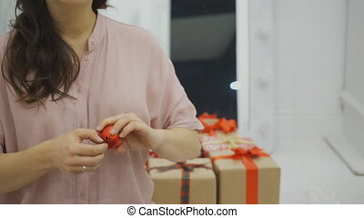 Woman is twirling in arms a red Christmas tree decoration in form of ball.