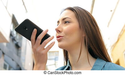 Woman is using voice recognition on smart phone standing in...