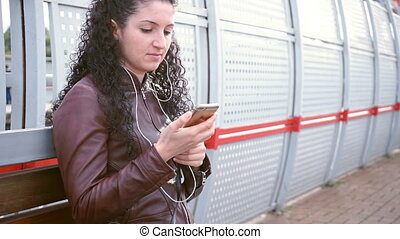 Woman is waiting for train and writing an sms