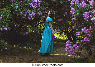Woman is walking in the garden of lilac.