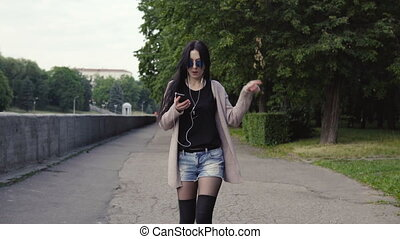 woman is walking in the park and dancing