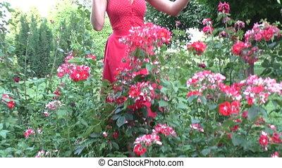 Woman is watering flowers. - Woman is watering flowers in a...